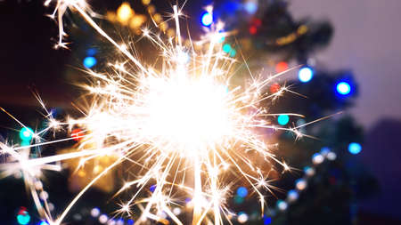 Sparkler - blurry background. Christmas lights, new year concept, festive bright wallpaper