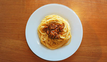 Plate of delicious spaghetti Bolognaise or Bolognese with savory minced beef and tomato sauce garnished, overhead view Stock Photo