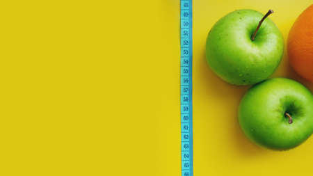 A green apple with measurements isolated on a yellow background. fitness food.