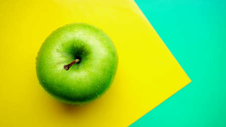 Green apple in water drops on yellow color background isolated close up macro top view 写真素材