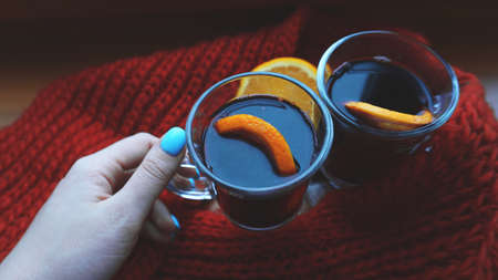 Woman holding mulled wine with spices and citrus fruit in her hand, close up Red Hot wine with orange and red scarf Stock Photo