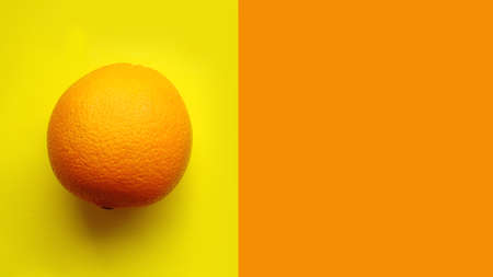 Whole orange fruit, top view. Isolated on yellow background isolated close up macro top view