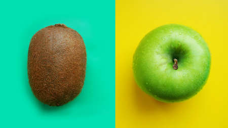 Green apple in water drops and kiwi on yellow and blue modern color background isolated close up macro top view
