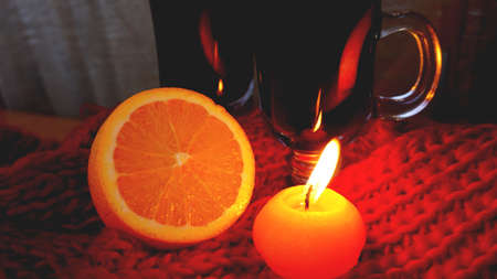 Mulled wine in glass mugs, burning candle on a dark red background. Red Hot wine with orange and red scarf