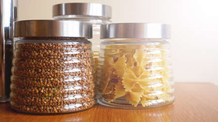 Pasta and bukwheat meals. Healthy cooking in glass jar containers on wooden table. Balanced dieting food. Stock Photo