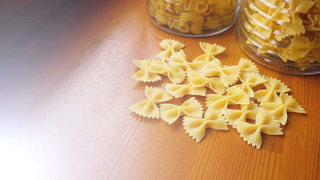 Pasta in the form of bows scattered from glass jar. Italian handmade pasta on the wooden background.