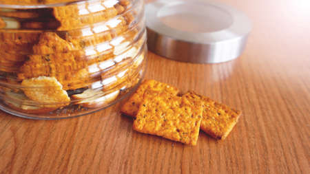 Wheat cracker in a glass jar on wooden table. The concept of kitchen and food