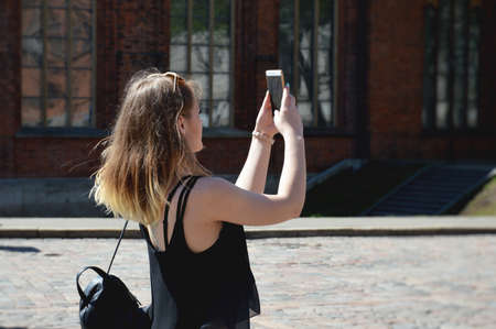 Young Girl Taking Photos Of City With Mobile Smart Phone. Beautiful young woman with smart-phone at the city street background Stock Photo