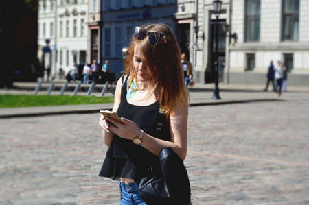 Beautiful young woman with blonde hair messaging on the smart-phone at the city street background. Pretty girl having smart phone conversation in sun flare.