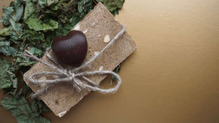 Organic handmade soap made of field herbs. Soap in a rope with dry grass and chocolate candy on a golden background Stock Photo