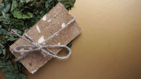 Organic handmade soap made of field herbs. Soap in a rope with dry grass on a golden background