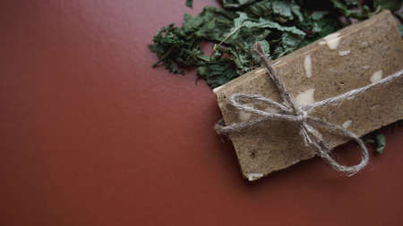 Organic handmade soap made of field herbs. Soap in a rope with dry grass on brown background Stock Photo