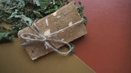 Organic handmade soap made of field herbs. Soap in a rope with dry grass on a golden and brown background