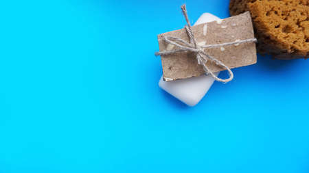 Gray and white Handmade soap wrapped with twine on a blue clean background Stock Photo