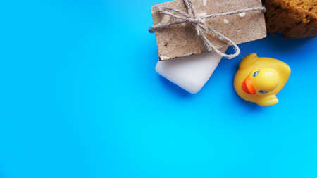 Gray and white Handmade soap and yellow toy duck on a blue background. Flat lay photo, top view