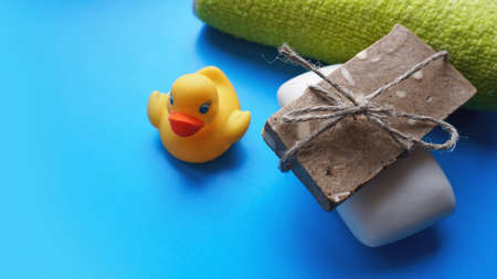 Terry towel, Gray and white Handmade soap and yellow toy duck on a blue background. Flat lay photo, top view