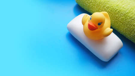 Terry towel, soap and yellow toy duck on a blue background. Flat lay photo, top view