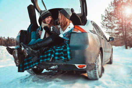Happy friends in winter forest in the car. Two happy girls sit in the trunk of a car drinking coffee, talking and laughing. Stock Photo