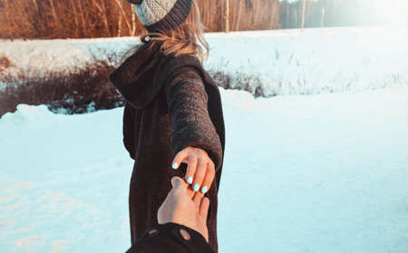 Follow me girl holding boyfriend hand in winter snow forest. Vintage look, holidays, romantic mood, love. Winter white trees landscape. Stock Photo