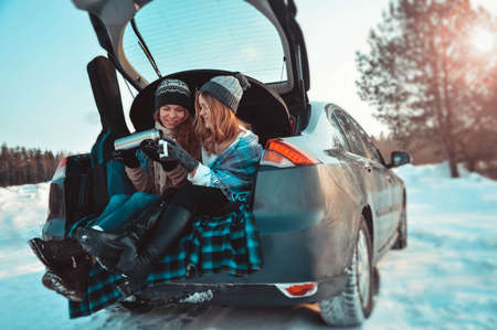 Gelukkige vrienden in het winterbos in de auto. Twee gelukkige meisjes zitten in de kofferbak van een auto koffie te drinken Stockfoto
