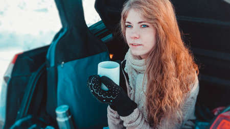Happy girl in knitted clothes, scarf and plaid sitting on truck of car in winter forest with a cup of hot tea or coffee, a guitar in the background - Travelling by car