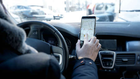 Transport, destination, modern technology and people concept - male hand searching for route using navigation system on car mobile screen