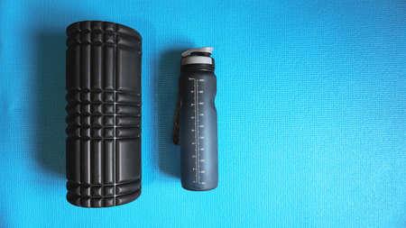 Foam Roller with water bottle Gym Fitness Equipment Blue background self Myofascial Release - MFR.
