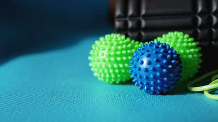 Massage ball and roller for self massage, reflexology and myofascial release, blue background. Equipment for sports, yoga, fitness