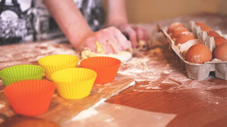 Cooking and home concept - close up of female hands kneading dough at home. Soft focus
