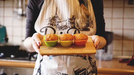Homemade caramel muffins in a baking dish in the hands of the confectioner. Dessert for gourmet. Selective focus 写真素材