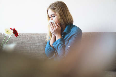 Spring cold or allergies. A young attractive girl is allergic to flowers, uses a napkin at home