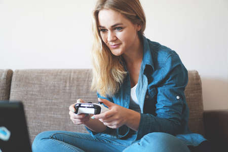 Girl gamer plays with a wireless gamepad while looking at the screen in front of her. Young blonde girl smiles and enjoys playing video games console.