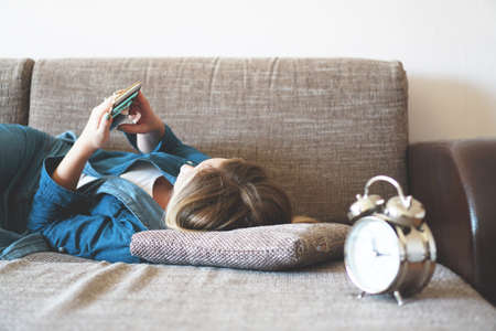 Young woman using phone in bed, looking at screen, insomnia, check time, wake up with smartphone, mobile phone addiction - alarm clock near Stock fotó