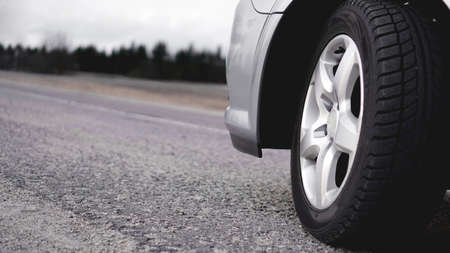 Close up of Wheel of silver car on the road. Photo in gray tones