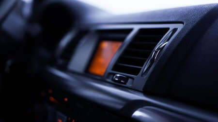 Buttons of radio, dashboard, climate control in car close up - black and orange
