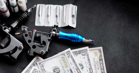 Tattoo machines on a black background and dollars. Tattoo art concept. Money for tattoo Reklamní fotografie