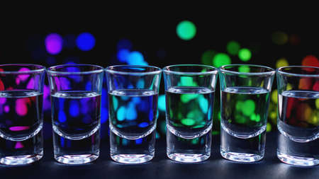 Glasses of vodka or tequila. In bar - neon background