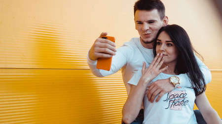 Young lovely couple posing together while making selfie on smartphone over yellow background