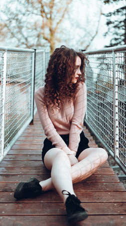 Fashion portrait of trendy young woman sitting near the netting rabitz in the city Stock Photo