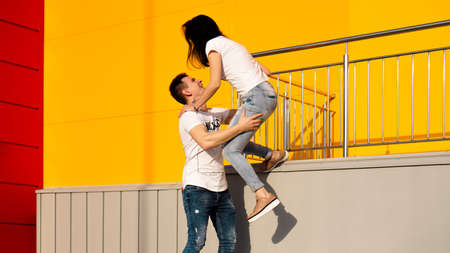 Happy man carrying his girlfriend on yellow background - couple in love