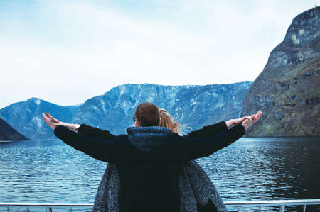 Couple travels by sea ferry in Norway. Fjords and mountains. A couple is standing backs and holding hands. Hands in different directions.
