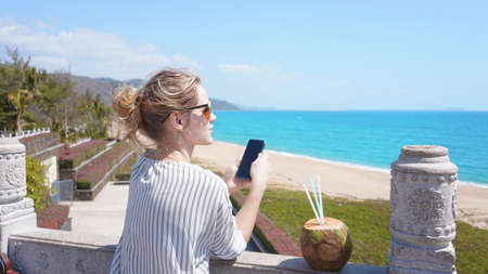 A beautiful young woman on a tropical beach with a phone in her hands. Rest, vacation, resort, beautiful life 写真素材