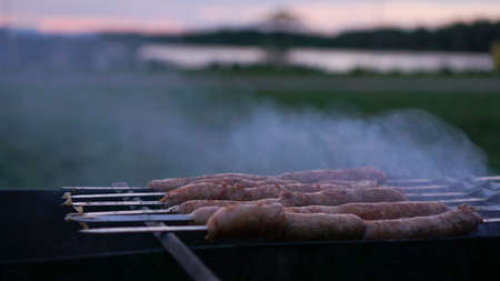 Grilling sausages at sunset outdoors gathering with friends and family. Sunner time