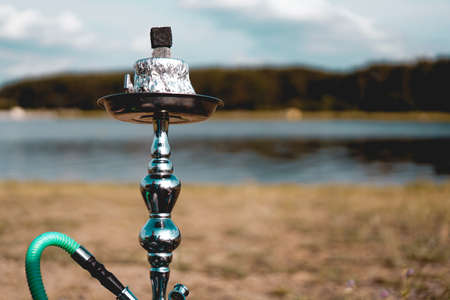 Summer vacation, activity. environment, travel and hookah smoking concept. Hookah bowl stands in nature by the river close up
