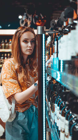 Young beautifull woman is choosing wine in the supermarket.