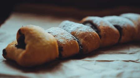 Rotoli al cioccolato appena sfornati con un delizioso ripieno, spolverati di zucchero a velo. Sullo sfondo di carta artigianale marrone Archivio Fotografico