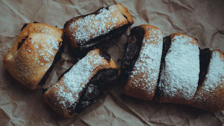 Freshly Baked Chocolate Rolls with a delicious filling, sprinkled with powdered sugar. Against the background of brown craft paper