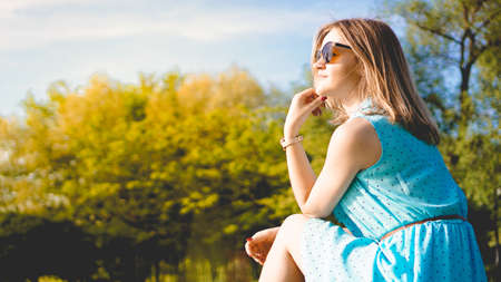 Young woman in sunny garden. Outdoor summer day. Meditation and freedom concept Stock Photo