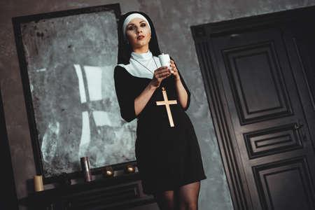 Junge katholische Nonne hält Kerze in ihren Händen. Foto auf schwarzem Hintergrund. Porträt einer schönen Frau