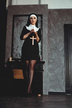 Junge katholische Nonne hält Kerze in ihren Händen. Foto auf schwarzem Hintergrund. Porträt einer schönen Frau Standard-Bild